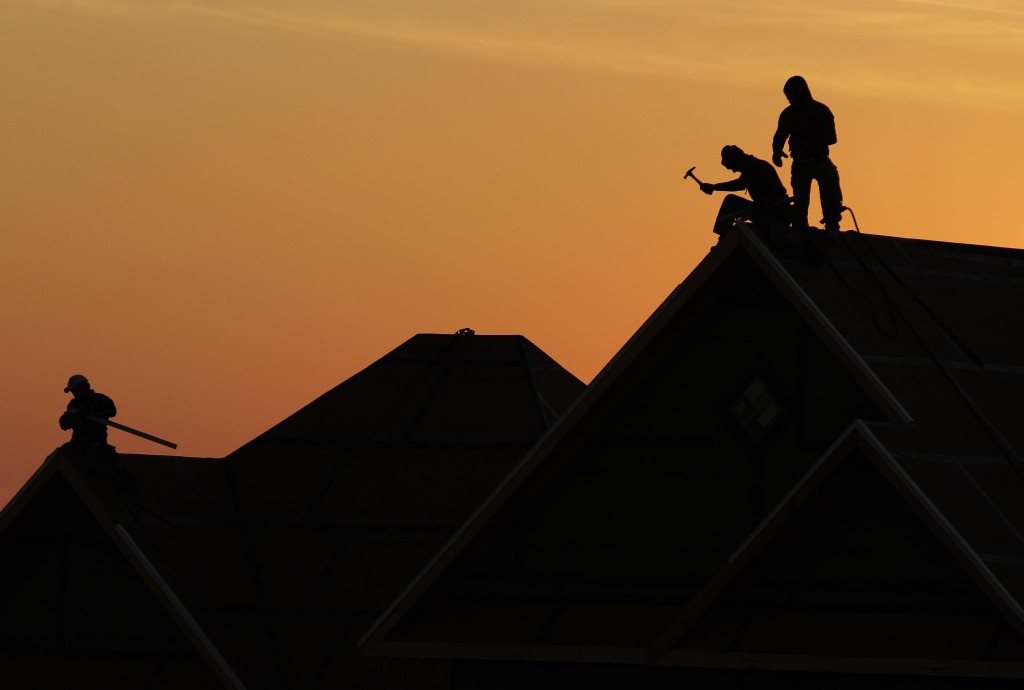 Workers are silhouetted as they build a home in Joplin, Mo., Thursday, Jan. 19, 2012. The city has issued nearly 4,000 building permits to homeowners since the an EF-5 tornado hit on May 22, 2011. (AP Photo/Charlie Riedel)