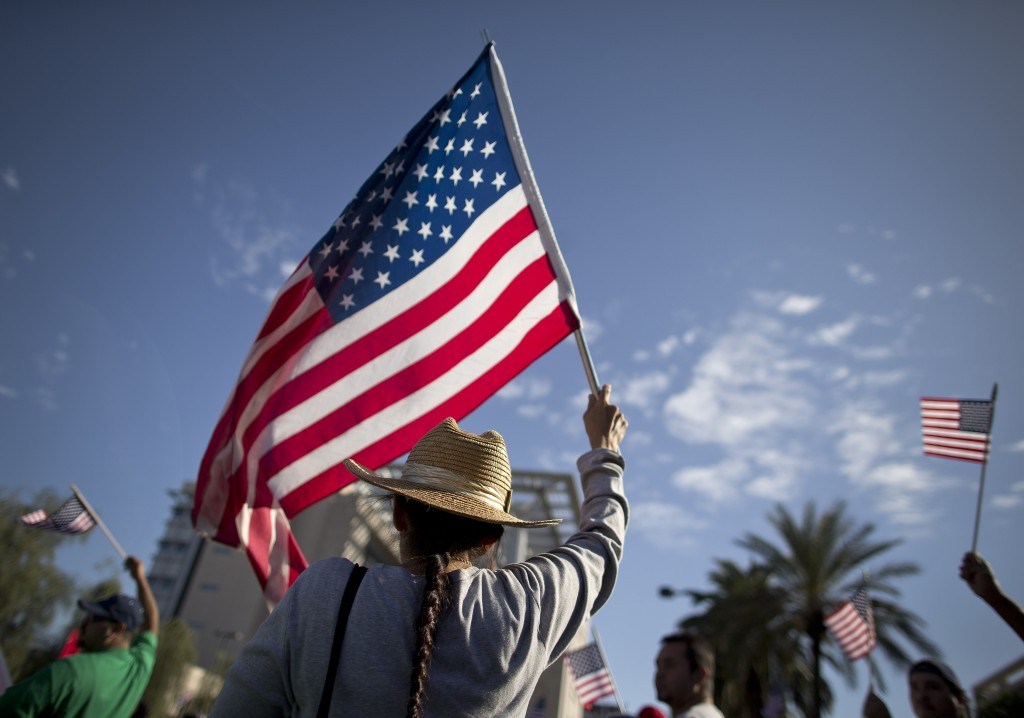 A demonstrator waves a flag during an immigration rally on May 1, 2013, in Las Vegas.