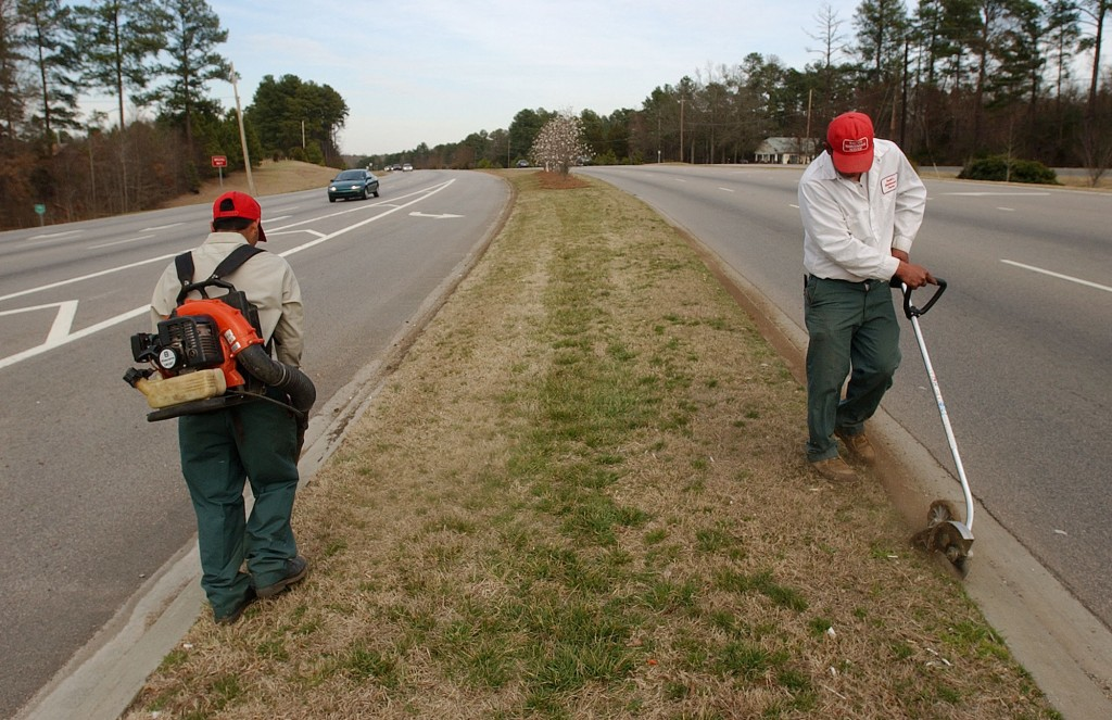 **ADVANCE FOR WEEKEND EDITIONS MARCH 19-20**  An unidentified Hispanic man, right, uses a gasoline edger to cut grass along a curb as his co-worker uses a gasoline blower to clean the opposite curb Tuesday, March 15, 2005 along N.C. State Route 54 in Durham, N.C. Manual labor for immigrants, even those who speak English, may offer more opportunity for some than seaking education. Many never enroll in school or drop out because of the pressure to earn money to help families here and back in their nativecountries. (AP Photo/Jeffrey A. Camarati)