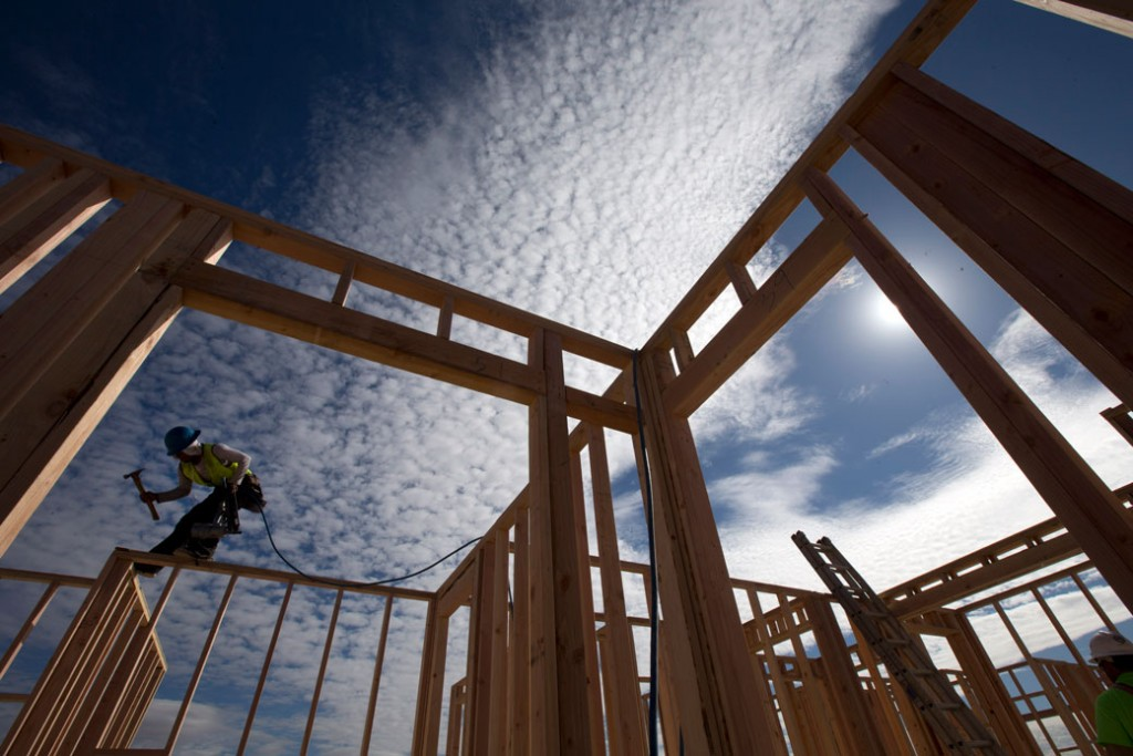 A construction worker works on a house frame for a new home in Chula Vista, California.