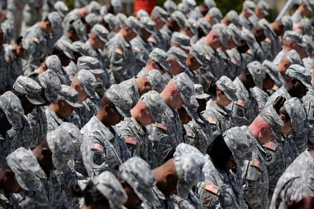 Soldiers bow their heads during a memorial ceremony for shooting victims on April 9, 2014, at Fort Hood, Texas.