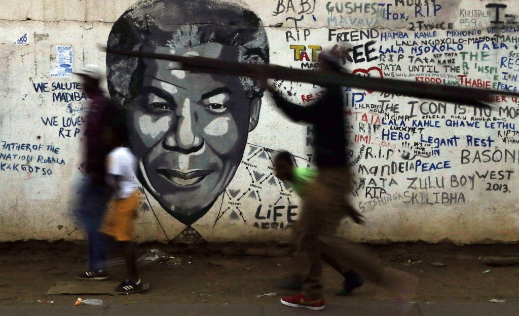 People walk past a mural of former South African President Nelson Mandela in Katlehong, south of Johannesburg, South Africa, May 2015.