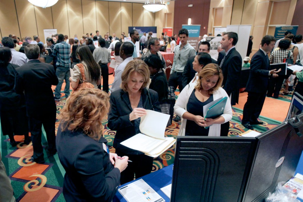 Job applicants visit various booths representing companies looking for employees or training schools at a job fair in Orlando, Florida.