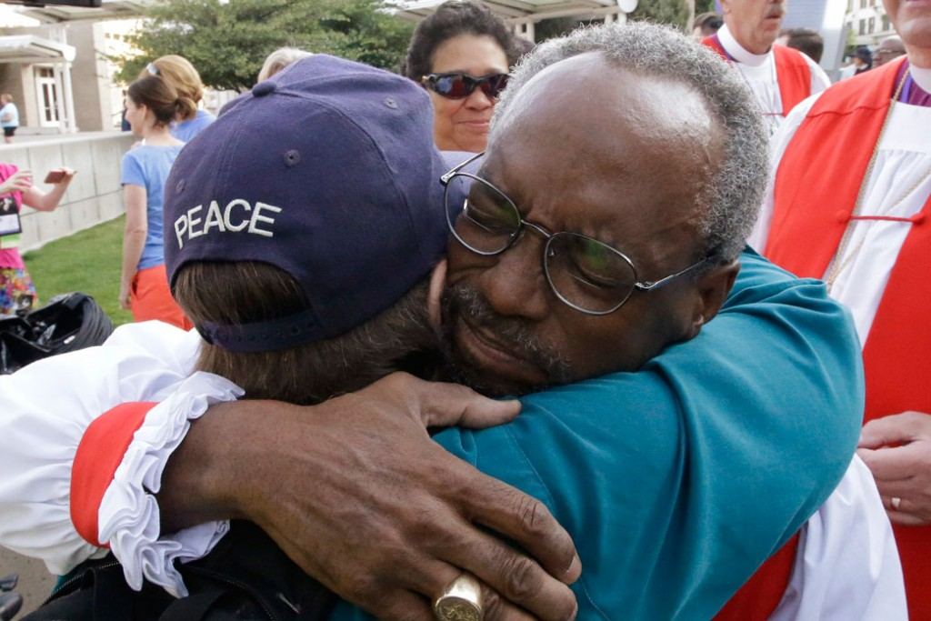 The Rev. Michael Curry gives a hug before a march and rally against gun violence, on June 28, 2015.