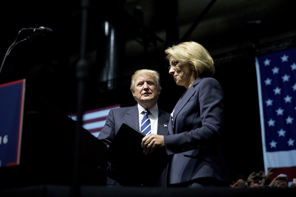 Then-President-elect Donald Trump, center, welcomes his pick for education secretary, Betsy DeVos, right, to the stage during a rally at DeltaPlex Arena, December 9, 2016, in Grand Rapids, Michigan.