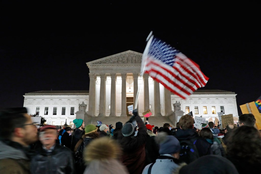 A protester waves an American flag in front of the Supreme Court during a protest about President Donald Trump's recent executive orders, January 2017.