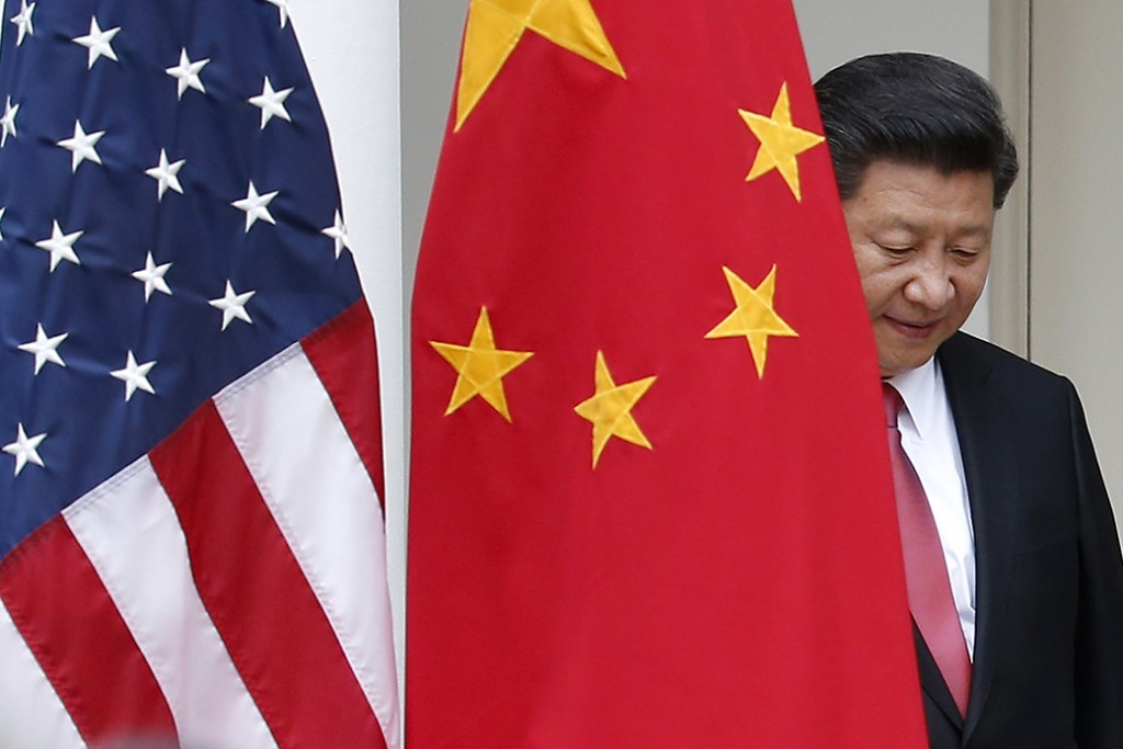 Chinese President Xi Jinping steps out from behind China's flag as he takes his position for a news conference in the Rose Garden of the White House in Washington.