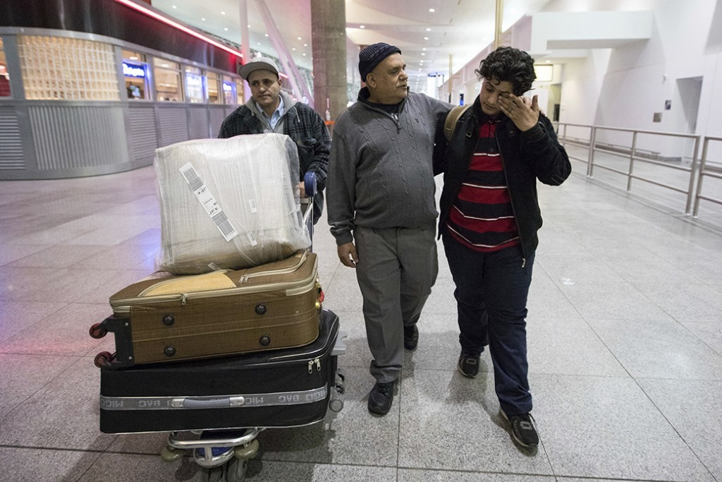 A teenage boy from Yemen wipes his eyes as he walks with his father and his uncle after arrival at John F. Kennedy International Airport in New York, February 5, 2017.