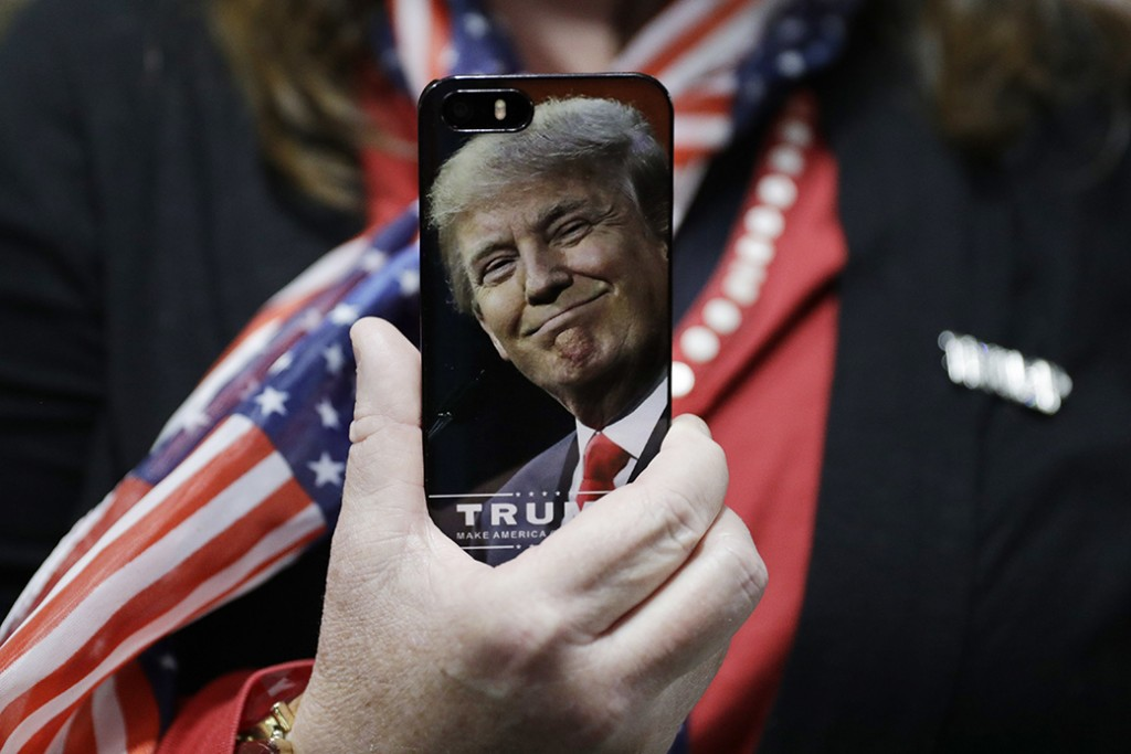 A woman holds up her cell phone before a rally with then-presidential candidate Donald Trump in Bedford, New Hampshire, September 29, 2016.