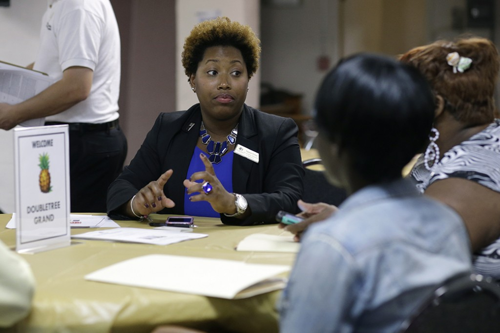 A human resources director talks with job applicants during a job fair, January 2015.