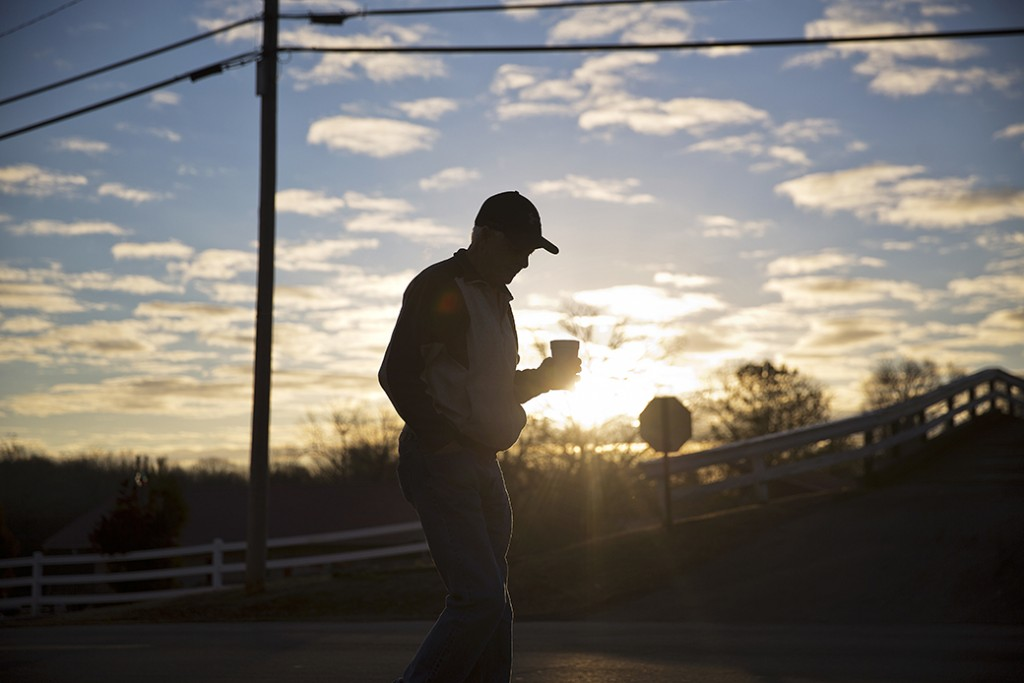 A man walks with a cup of coffee after dropping his car off for repair as the sun rises in Lula, Georgia, January 12, 2017.