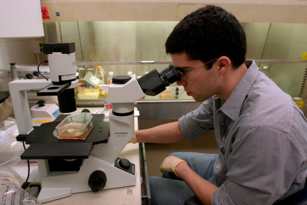 A Duke University student looks at the density of cells through a microscope in Durham, North Carolina, in February 2008.