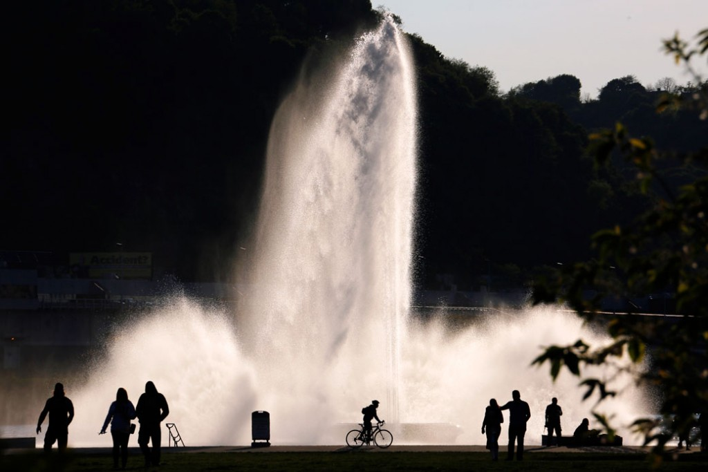 Visitors to Point State Park are silhouetted against a fountain in downtown Pittsburgh on May 8, 2016.