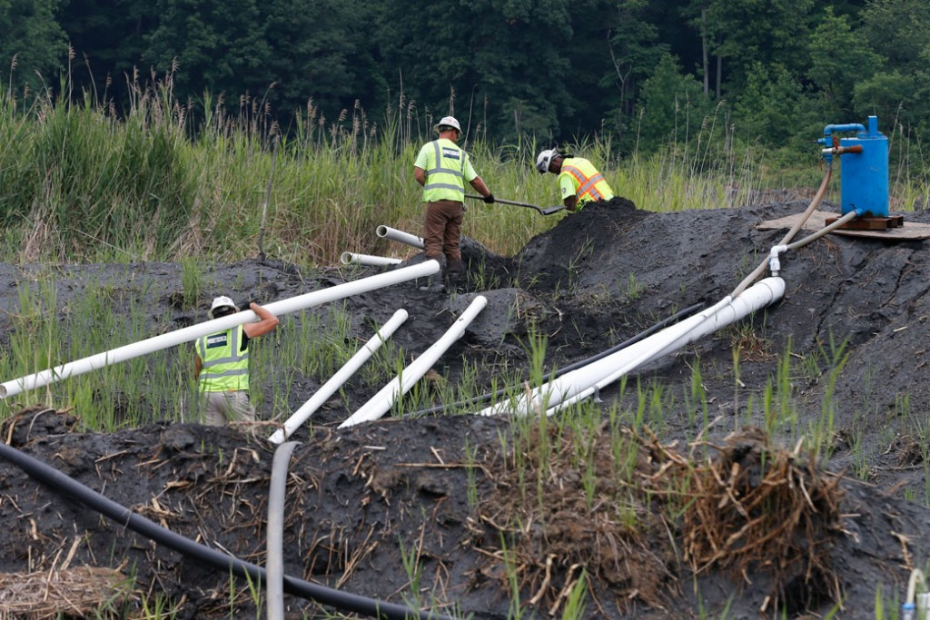 Workers install a drainage system in a coals ash retention pond at the Dominion Power's Possum Point Power Station in Dumfries, Virginia, on June 26, 2015.