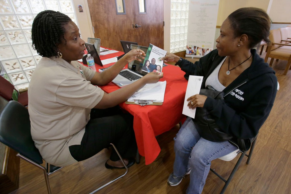 Suze Diogene, left, a certified application counselor, gives Audrey Allen information about health care, on October 1, 2013, in Miami.