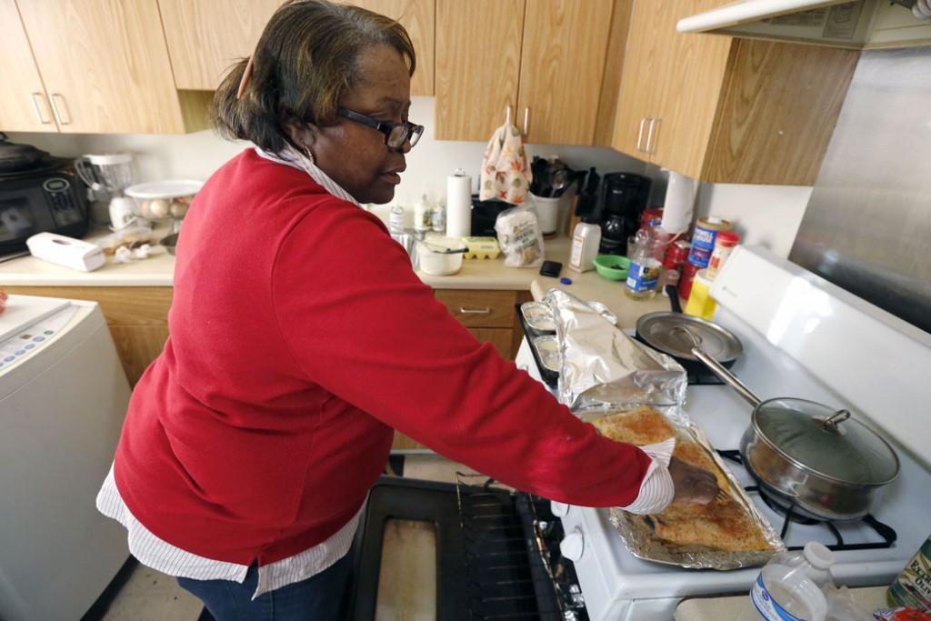 Debra Aldridge begins dinner for her and her grandson, Mario, at her home on Chicago's South Side on January 29, 2016.