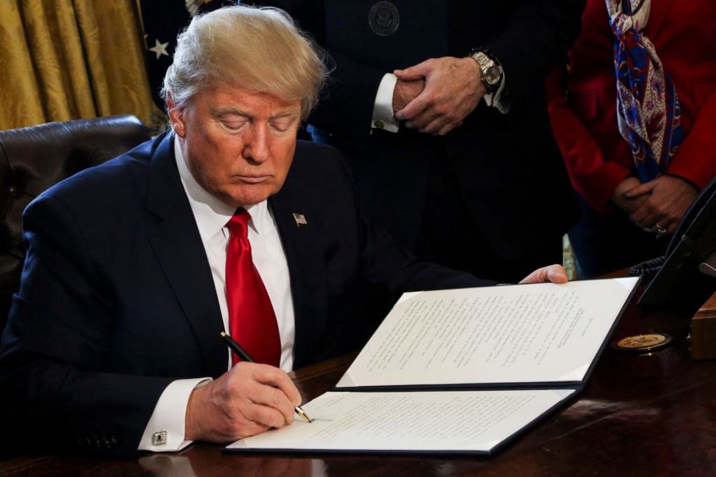 President Donald Trump signs an Executive Order in the Oval Office of the White House, to review the Dodd-Frank Wall Street to roll back financial regulations of the Obama administration on February 3, 2017.