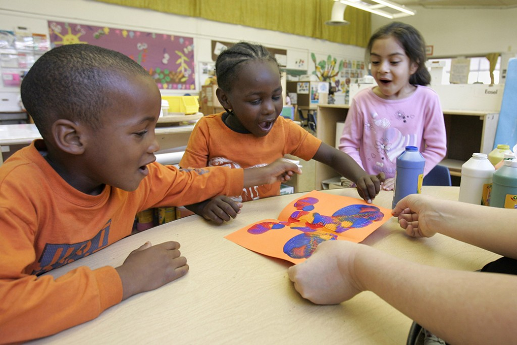 Preschoolers Raymond Gilliam, left, Devon Edwards, center, and Hilda Torres look at the butterfly Edwards made for a Mother's Day card at a publicly funded preschool class in Sacramento, California, May 2006.