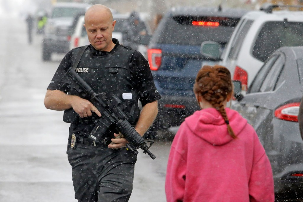 A police officer carries his weapon in front of Mueller Park Junior High after a student fired a gun into the ceiling in Bountiful, Utah in December 2016.