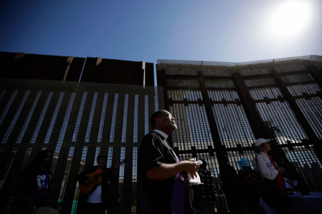 A reverend leads a song on the U.S. side of the border fence separating Tijuana, Mexico, from San Diego, April 3, 2017.