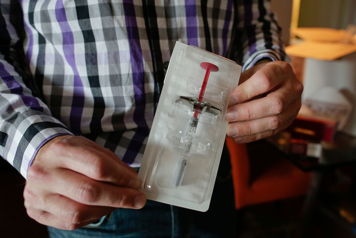 Brian Greenberg, who suffers from Crohn's disease, holds up a syringe preloaded with his prescription medication that was delivered to his home in Stamford, Connecticut, July 6, 2016.