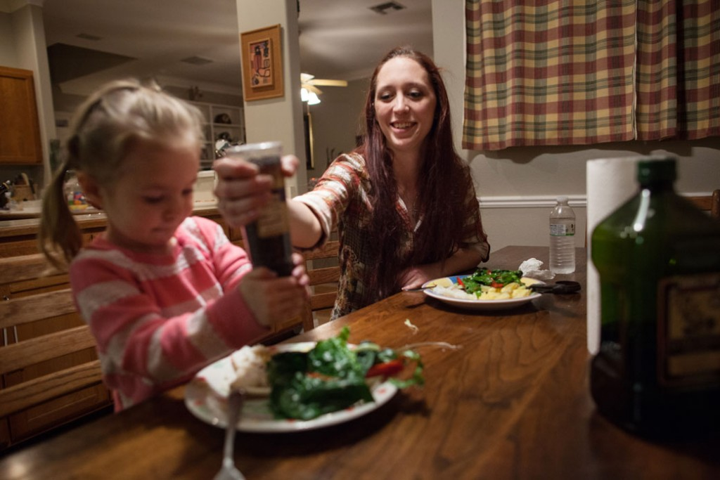 A mother helps her daughter use a pepper grinder at dinner in Austin, Texas, January 25, 2014.