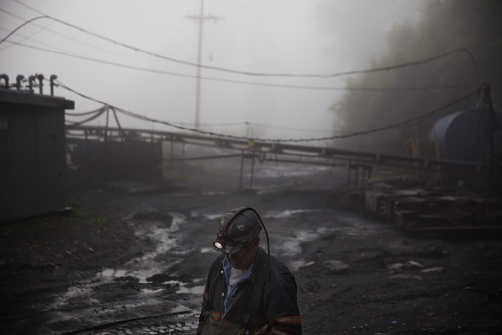 CLIMATE CHANGE: In this Thursday, May 12, 2016 photo, coal miner Scott Tiller walks through the morning fog before going underground in a mine less than 40-inches high in Welch, W.Va. For over a century, life in Central Appalachia has been largely defined by the ups and downs of the coal industry. There is a growing sense in these mountains that for a variety of reasons, economic, environmental, political, coal mining will not rebound this time. Coal's slump is largely the result of cheap natural gas, which now rivals coal as a fuel for generating electricity. Older coal-fired plants are being idled to meet clean-air standards. According to the Labor Department, there were 56,700 jobs in coal mining in March, down from 84,600 in March 2009, shortly after President Barack Obama entered office. There are stark differences between the two parties on energy and environment issues that underscore the sky-high stakes for both sides of the debate in the 2016 presidential race. Many environmental groups and Democrats fear a potential rollback of the Obama administration's policies on climate change and renewable energy under a Republican president. Republicans all support coal production and enthusiastically back nuclear energy. They along with business groups are eager to boost oil and gas production following years of frustration with Obama. (AP Photo/David Goldman)