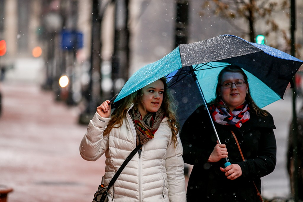 Two women share an umbrella in Washington, March 5, 2015, as snow begins to fall.