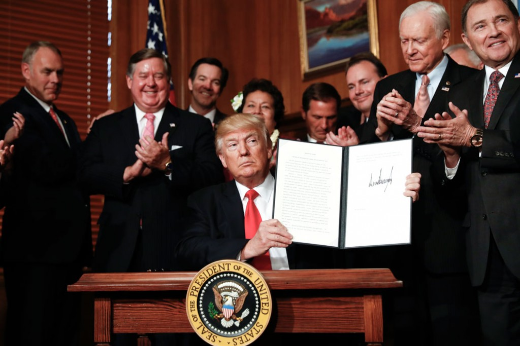 President Donald Trump holds up the signed executive order on the Antiquities Act during a ceremony at the Interior Department on April 26, 2017.