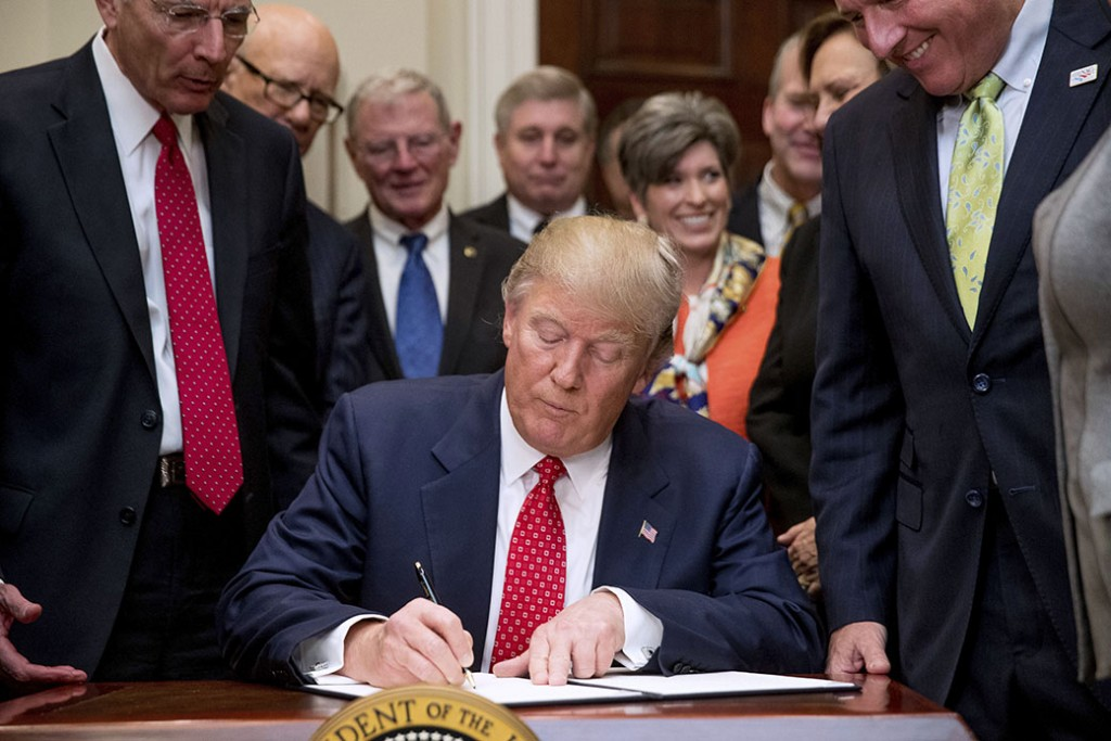 President Donald Trump signs the Waters of the United States executive order, February 28, 2017, in the Roosevelt Room in the White House in Washington.