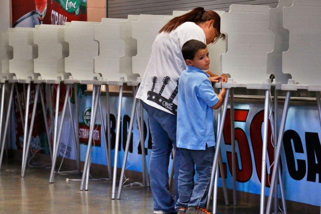 A woman completes her ballot as a child waits in Pueblo, Colorado, on September 10, 2013.