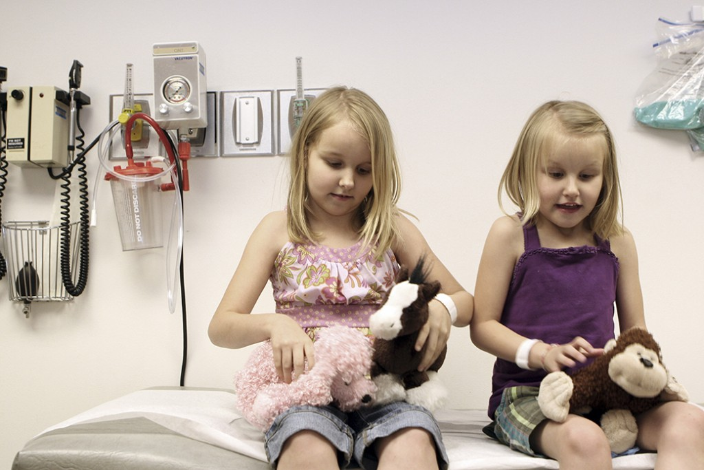 Sisters play with stuffed animals during a check-up with their pediatric cardiologist at a medical center in Dallas, April 2008.