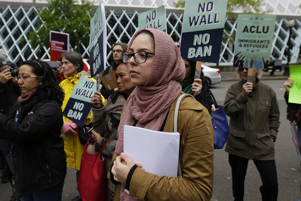 Isra Ayesh, center, of Seattle, who is the organizing director of Americans for Refugees & Immigrants, waits for her turn to speak during a demonstration against President Donald Trump's revised travel ban, May 15, 2017, outside a federal courthouse in Seattle.