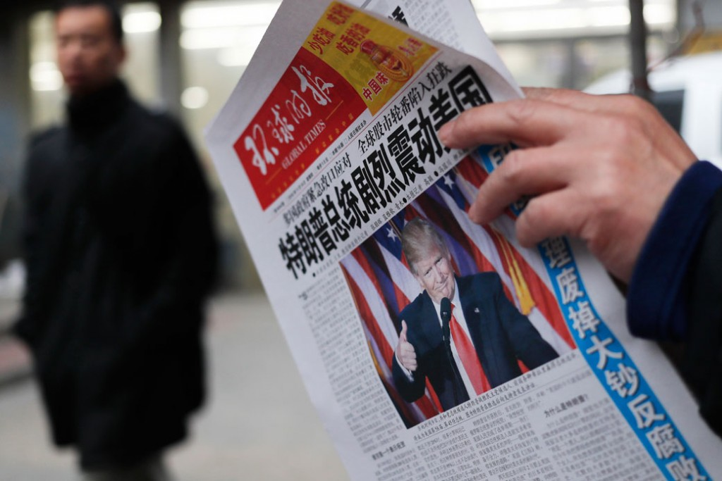 A man reads a newspaper in Beijing, November 10, 2016.