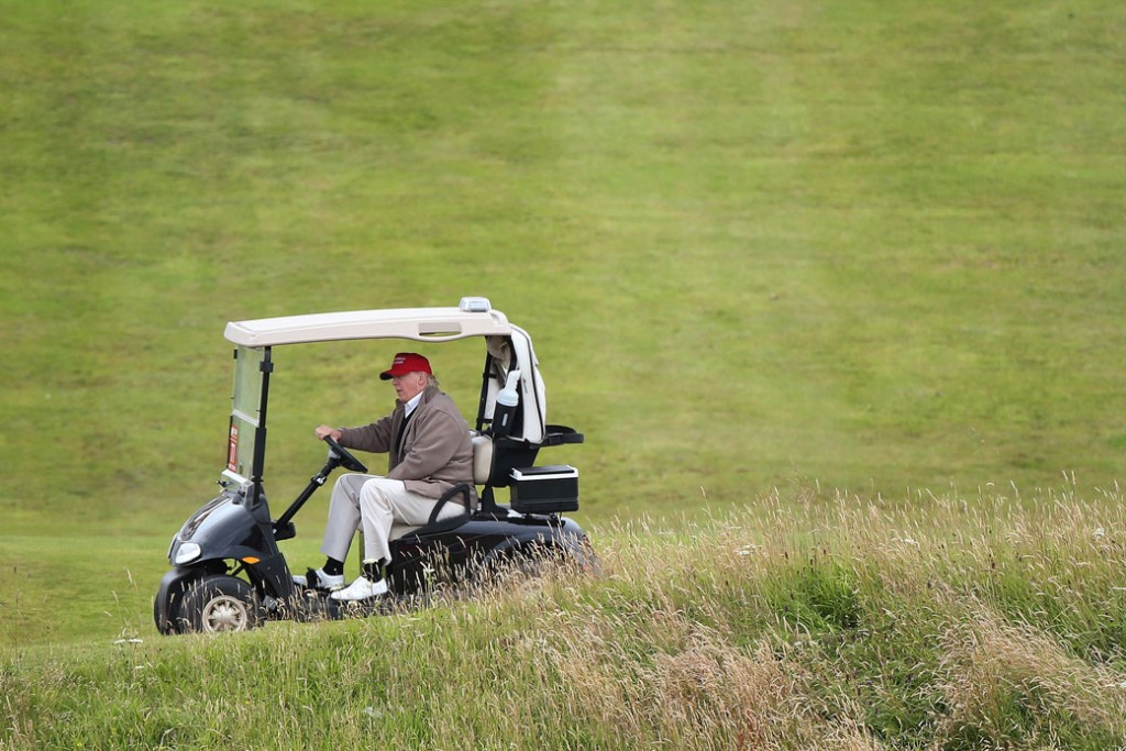 Then-presidential candidate Donald Trump drives his golf buggy on the Turnberry golf course in Scotland, July 31, 2015.
