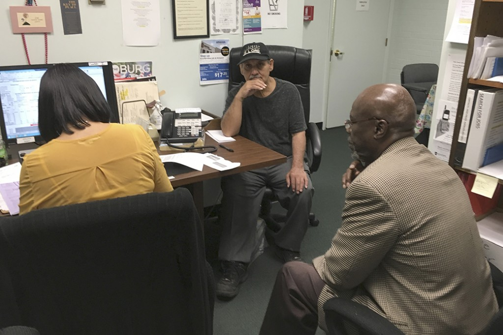 A social worker listens as an employment specialist interviews a program participant, center, at a foundation in Harrisburg, Pennsylvania, May 2017.