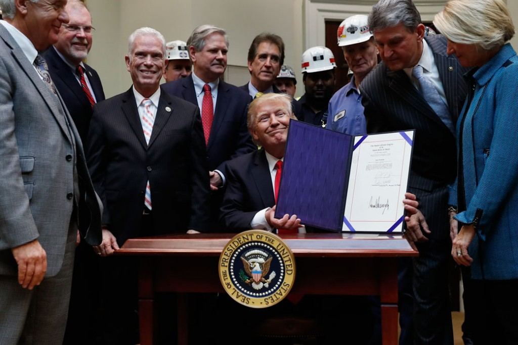 In this February 16, 2017, photo, Sen. Shelley Moore Capito (R-WV), right, Sen. Joe Manchin (D-WV), second from right, and coal miners watch as President Donald Trump holds up H.J. Res. 38 after signing it in the Roosevelt Room of the White House in Washington.