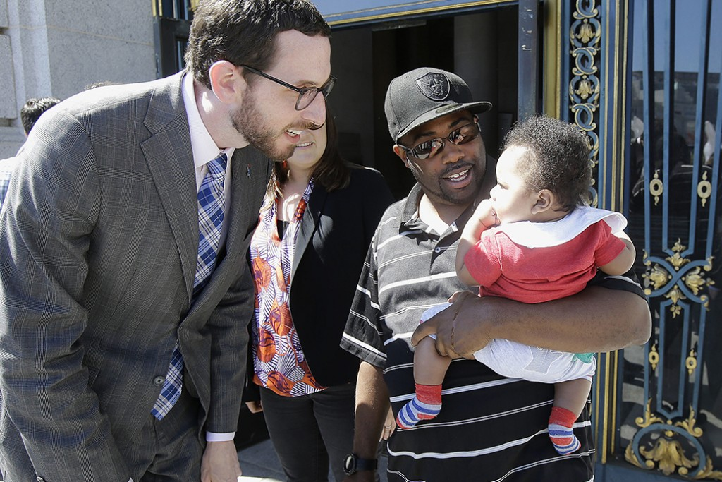 A father holds his 6-month-old son as he speaks with former San Francisco Supervisor Scott Wiener, left, before a rally supporting paid family leave at City Hall in San Francisco, April 5, 2016.