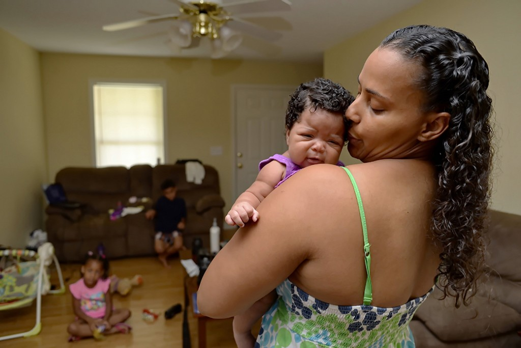A Mother holds her 2-month-old baby as her children sit in their home in Greenville, South Carolina, June 2014.