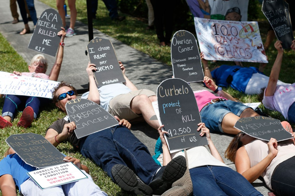 Demonstrators protest during a health care demonstration outside the offices of Rep. Carlos Curbelo (R-FL), Thursday, May 4, 2017, in Miami.