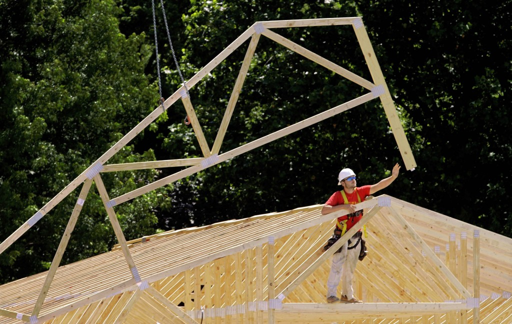A construction worker is seen installing roofing beams on an industrial park complex in Springfield, Illinois, May 16, 2012.
