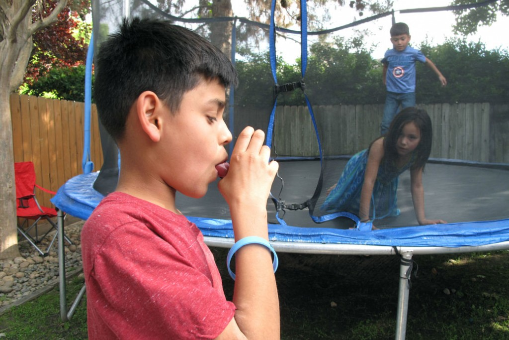 A boy in Fresno, California, demonstrates how he uses an inhaler to combat asthma, made worse by air pollution in San Joaquin Valley, April 2017.