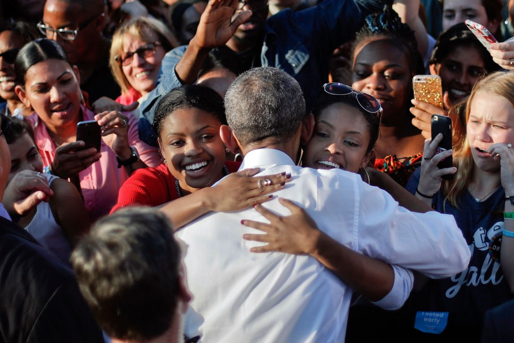 Two women embrace former President Barack Obama at the University of North Carolina, November 2, 2016.