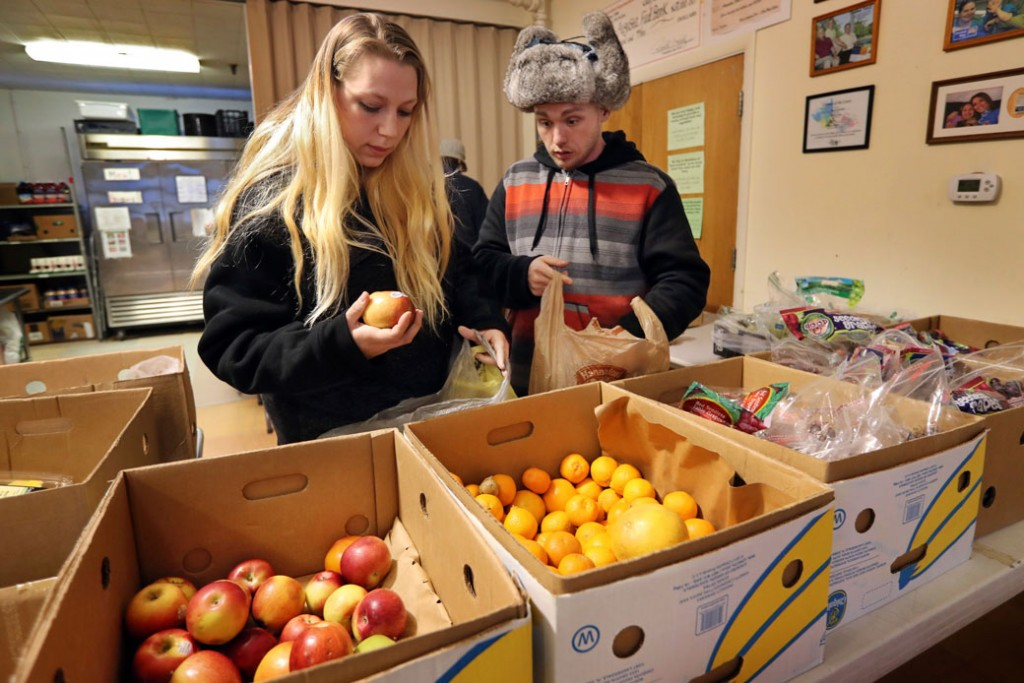 In this March 27, 2017, photo Sunny Larson, left, and Zak McCutcheon pick produce while gathering provisions to take home at the Augusta Food Bank in Augusta, Maine.