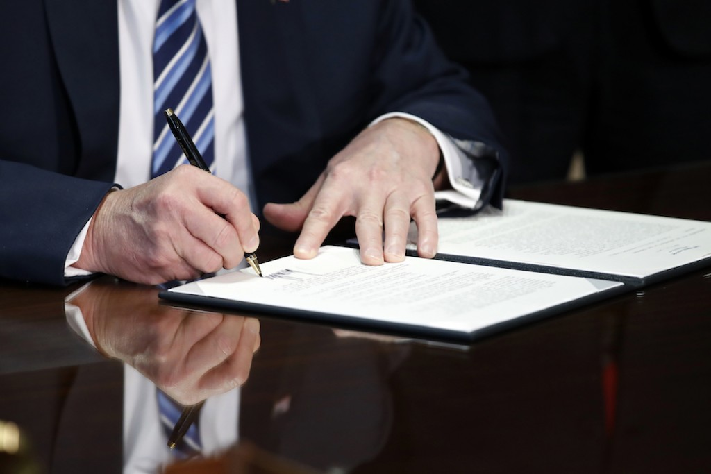 President Donald Trump signs an executive order at the U.S. Treasury Department in April 2017.