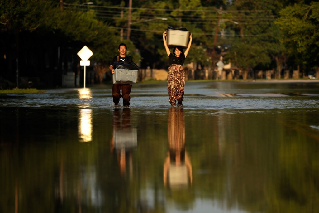 Mariko Shimmi, right, helps carry items out of Ken Tani's home in a neighborhood still flooded from Harvey on Monday, September 4, 2017, in Houston.