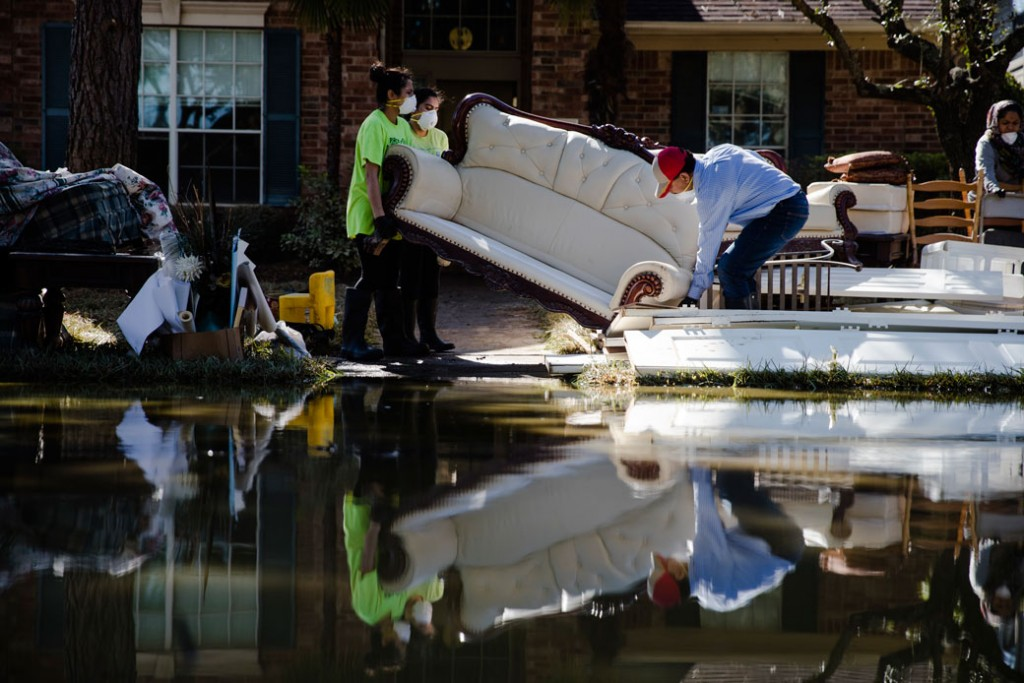 Sohail Soomro, center right, accompanied by his family, dumps flood damaged furniture on his front yard in the aftermath of Hurricane Harvey on Thursday, September 7, 2017, at the Canyon Gate community in Katy, Texas.