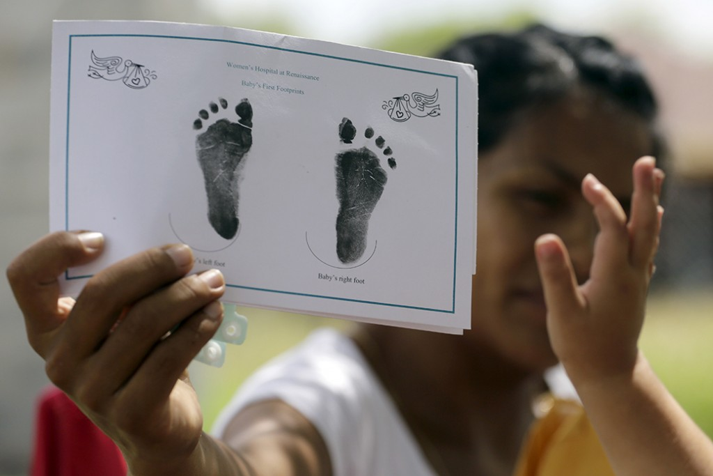 A woman shows the footprints of her daughter, reaching into photo,  in Texas, September 2015.