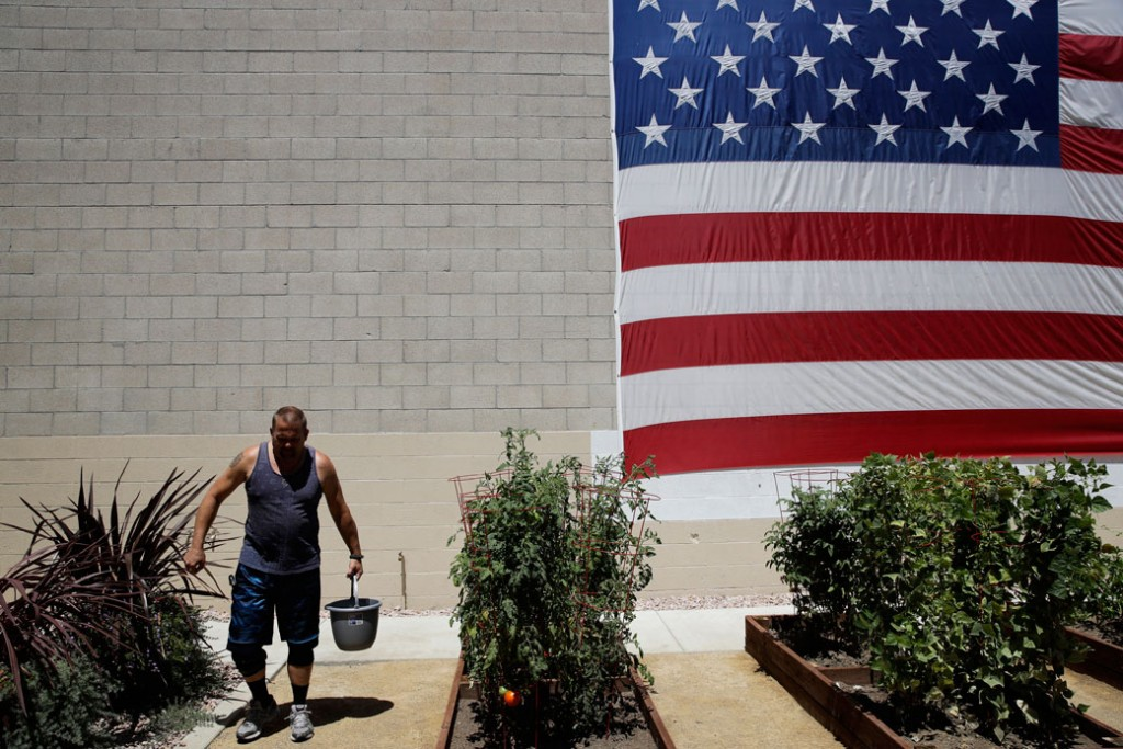 A giant American flag hangs on the wall of Potter's Lane, an apartment complex made out of recycled shipping containers just for homeless veterans, August 2017.