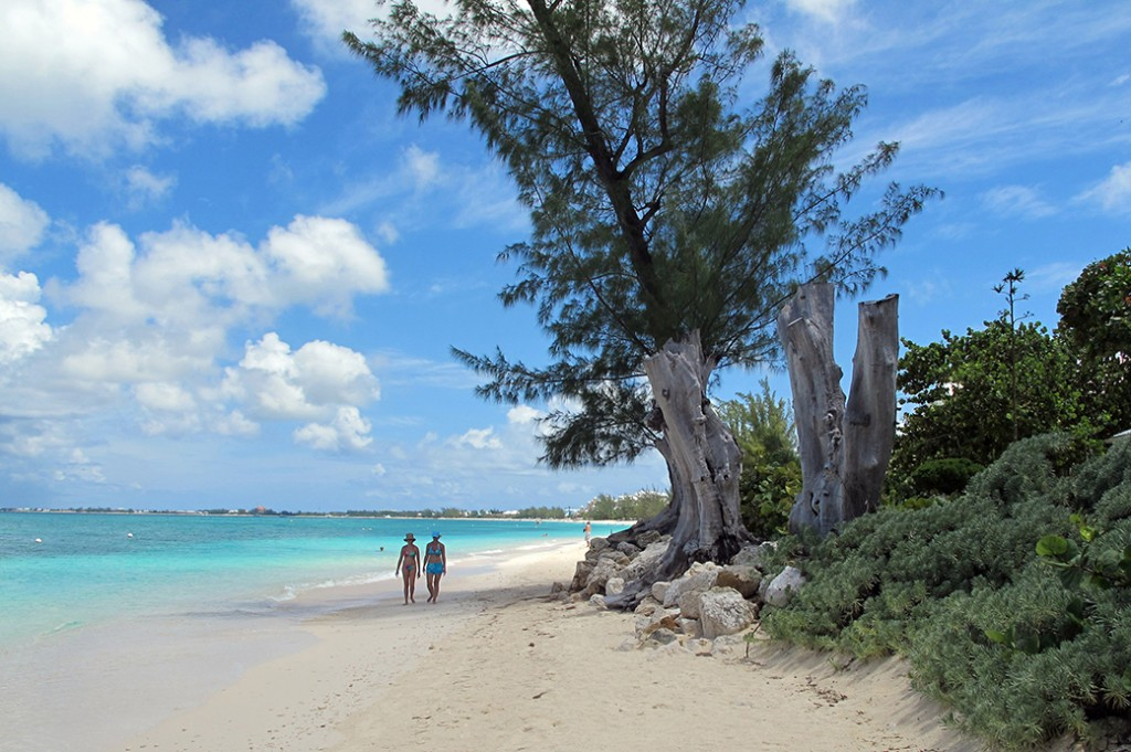 Tourists walk along the shore of Seven Mile Beach in Grand Cayman Island, August 2012.